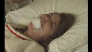Pretty brunette in Straitjacket taped mouth forced tied to bed hospital